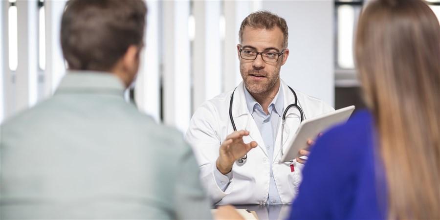 Arts in gesprek met twee patienten in de spreekkamer.