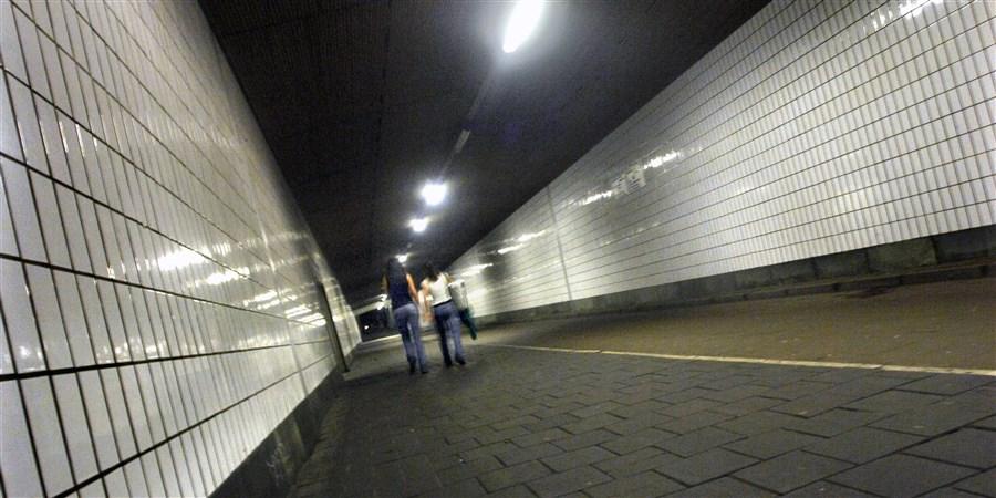 twee vrouwen lopen door tunnel  met beveiligingscamera's