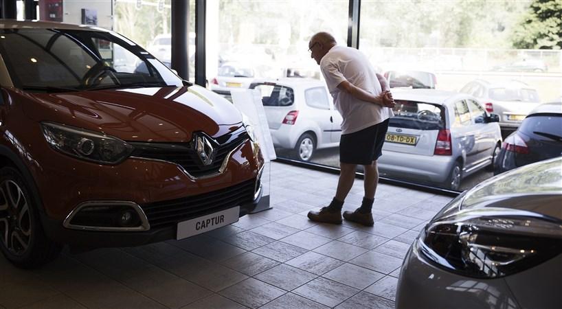 Man bekijkt auto bij autodealer in showroom