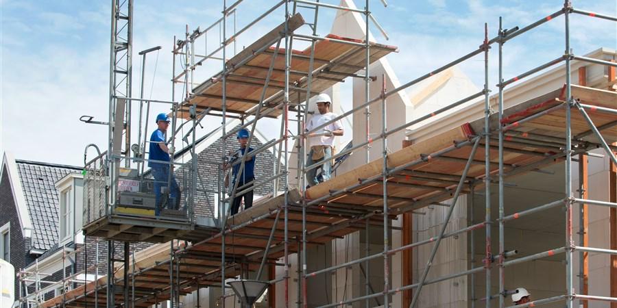 Bouwvakkers op steiger bij nieuwbouwwoningen