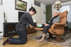 Vrouw helpt oudere vrouw met aantrekken kousen