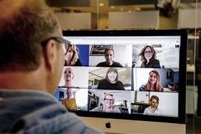 Een man vergadert op afstand met collega's via zijn laptop