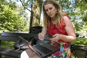 Jonge vrouw bezig op haar laptop op een bank in het park bezig bij de beveiligde website van haar bank in te loggen met een e dentifier om een betaling te doen.