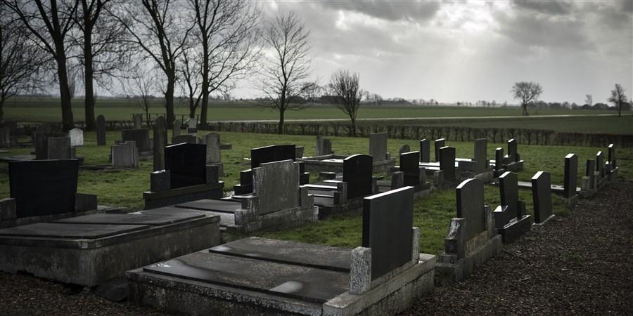 Begraafplaats met grijze lucht en donkere wolken