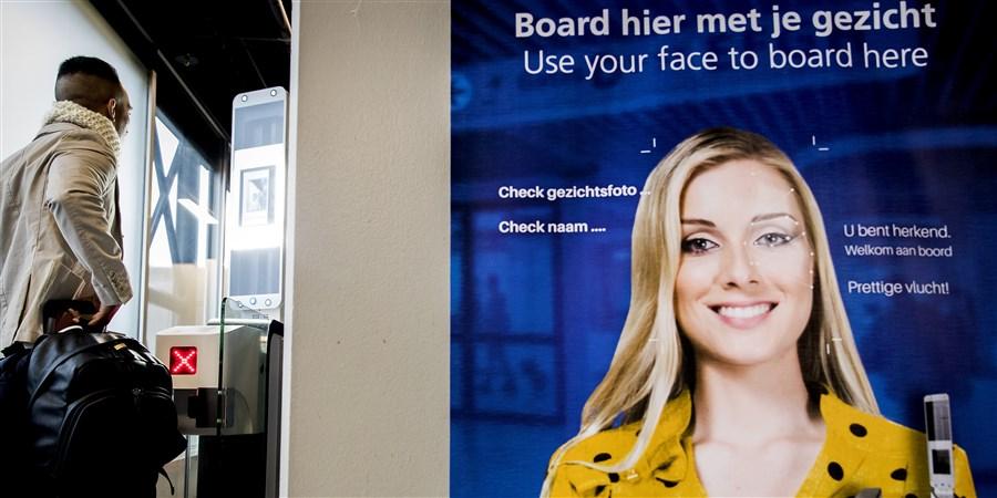 Man staat voor poortje waar gezicht automatisch gescand wordt. Automatisch boarden op luchthaven.