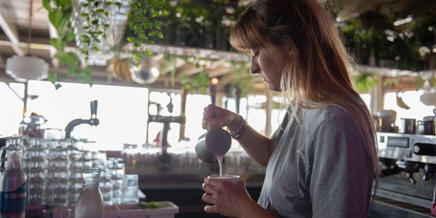Jonge vrouw werkt achter bar in strandpaviljoen