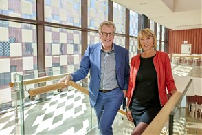 Mike Ackermans en Gabrielle van Mourik staan op de trap in het CBS gebouw in Den Haag.