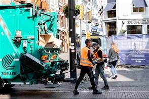 twee vuilnismannen die het karton in de winkelstraten van Den Haag ophalen