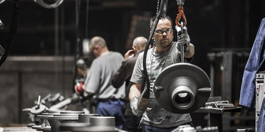 Arbeiders in Heerlense ijzergieterij gieten metalen onderdelen voor vrachtwagens etc
