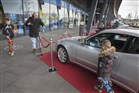 Man fotografeert kind voor auto