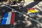 Mevrouw op de fiets die de grens tussen België en Nederland oversteekt.