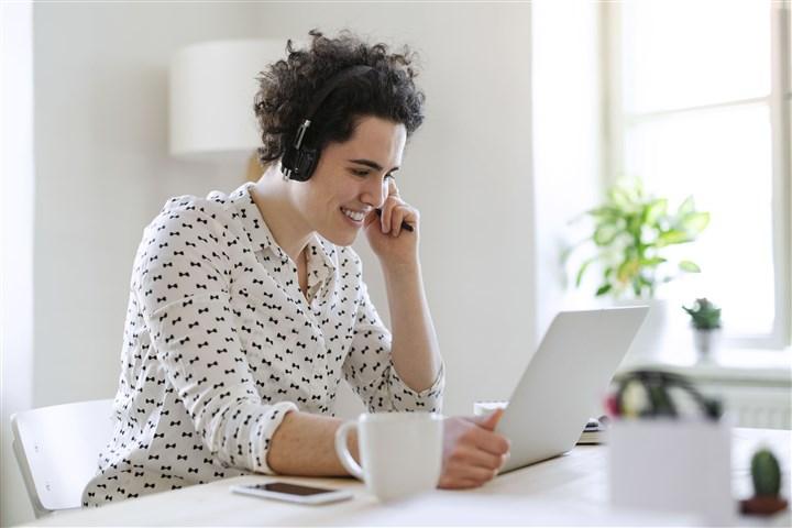 Glimlachende jonge vrouw met hoofdtelefoon en laptop die bij bureau werkt