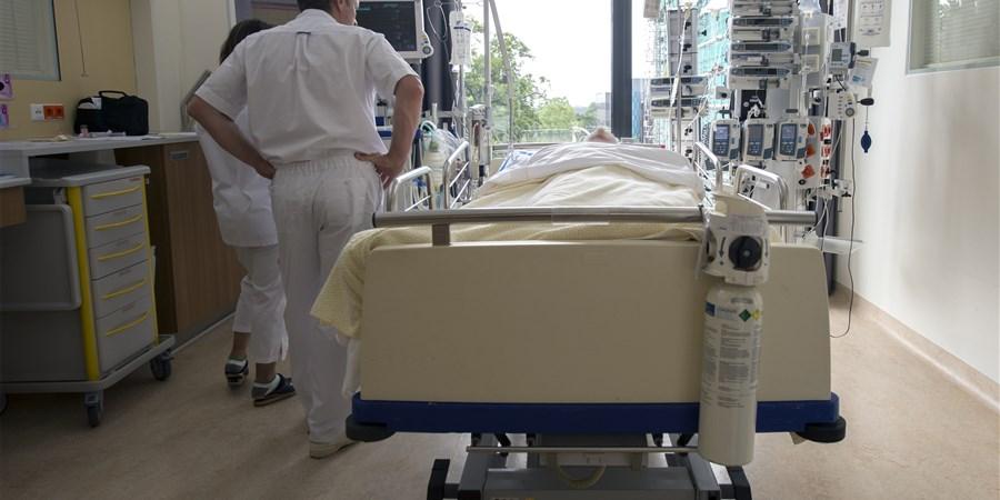Verplegend personeel naast een ziekenhuisbed op een Intensive Care kamer