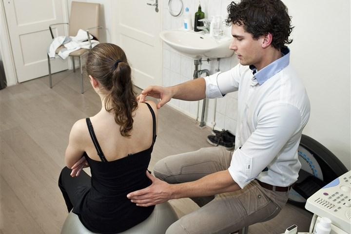 foto: Schouder en rug van dame onderzocht door arts