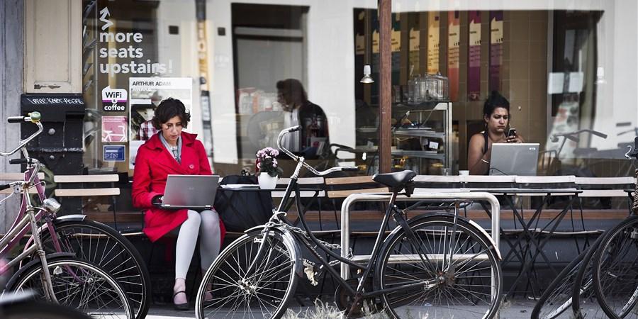 Twee vrouwen met een laptop, een binnen en een buiten een café met wifi