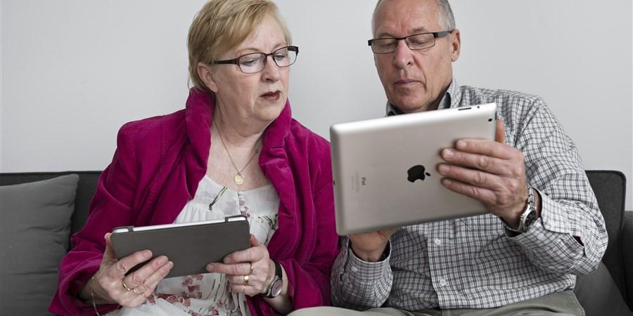 Ouderen die met ipad op de bank zitten en met elkaar meekijken