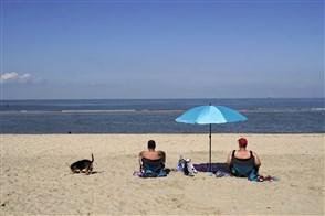 Man en vrouw onder parasol aan het strand