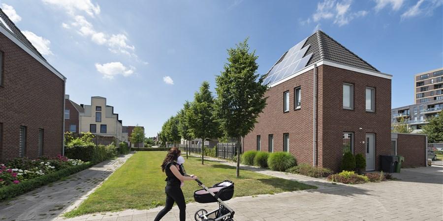 Vrouw met kinderwagen loopt langs energiezuinige woningen