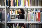 Dame zoekt in een kast met boeken