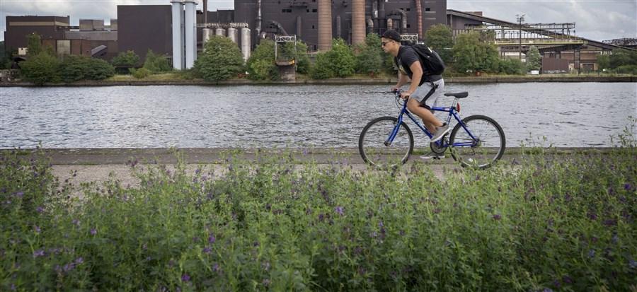 fietser op mountainbike fietst langs de maas met op de achtergrond een staalfabriek
