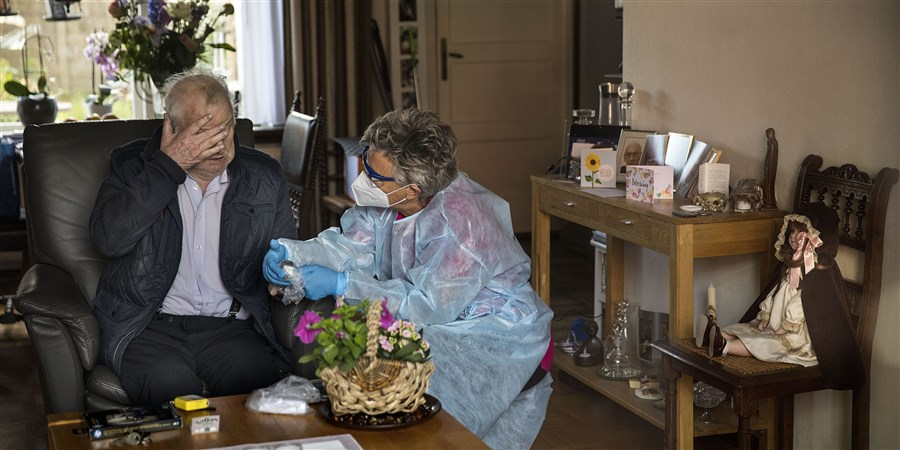 Medewerkster van thuiszorgorganisatie in beschermingskleding. Thuiszorg tijdens corona. Een man van 92 wordt thuis verzorgd.