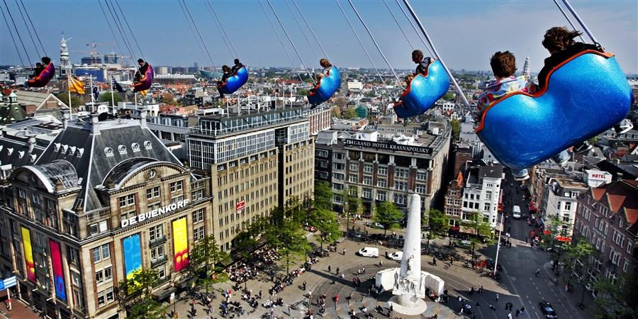 Uitzicht over Amsterdam vanaf zweefmolen op een kermis op de Dam