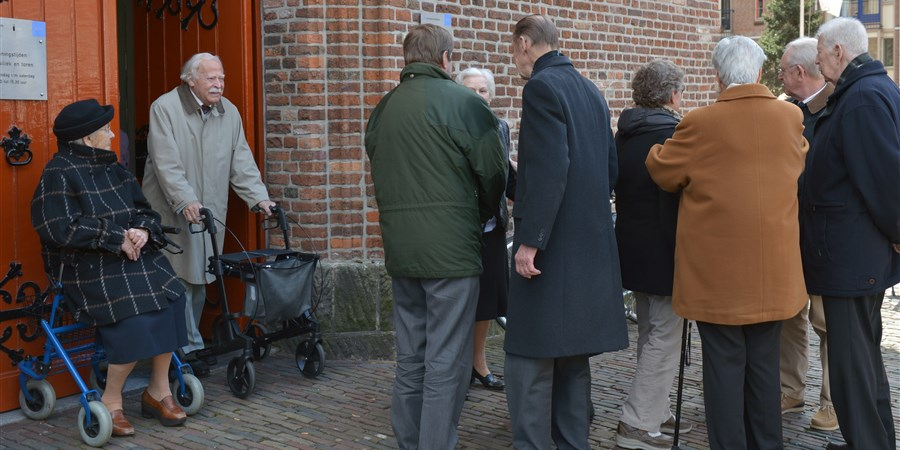 Een groep ouderen mensen pratend voor de kerk