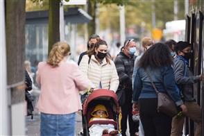 Mensen met mondkapje op wachten bij de tramhalte