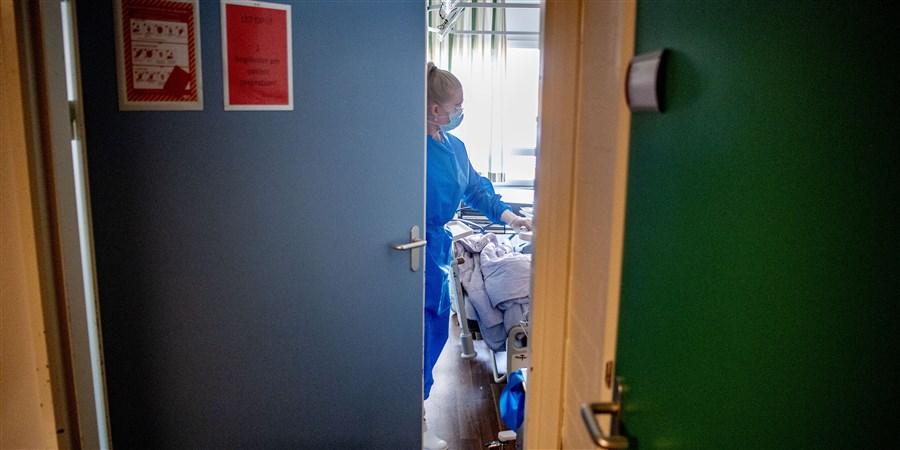 Verpleegkundige die aan het werk is in een kamer vanuit smalle deuropening gezien