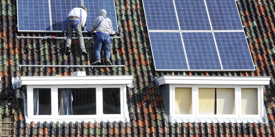 Monteurs plaatsen zonnecellen op schuin pannendak