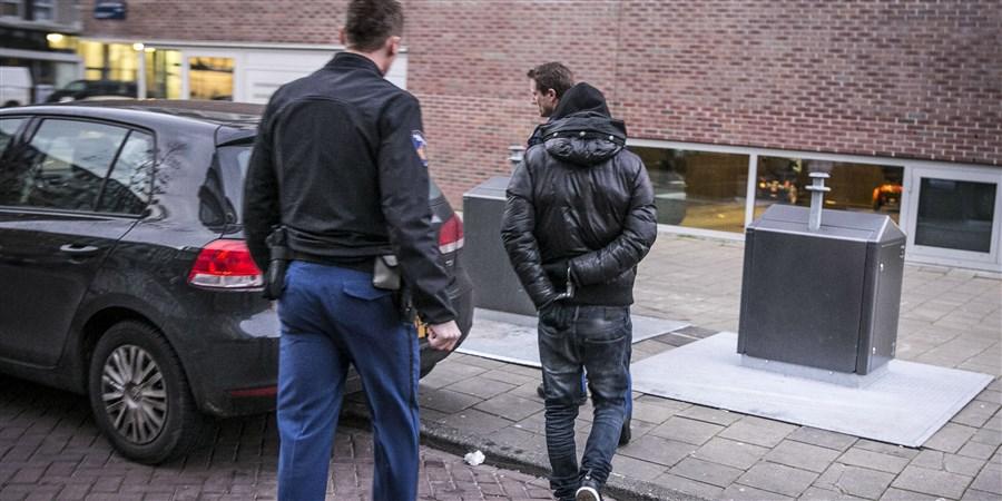 Een jongere wordt geboeid door 2 agenten weggevoerd.