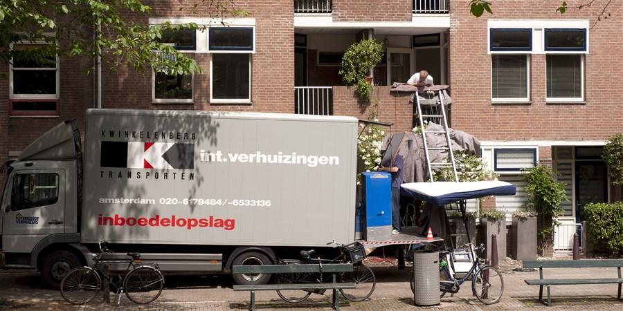 Internationale verhuiswagen op voorgrond, flat waaruit een matras wordt gehaald.