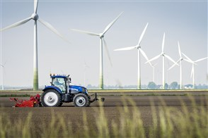 Tractor on farmland and wind turbines in the background