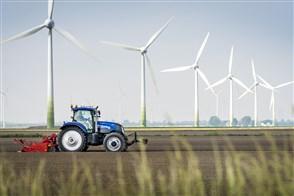 Tractor op het land, met op de achtergrond windmolens