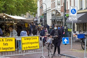 Winkelende mensen in het centrum van Delft. Veel mensen dragen mondkapjes.