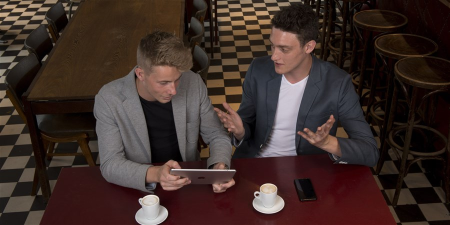 Jonge mannen in zakelijk overleg in cafe.