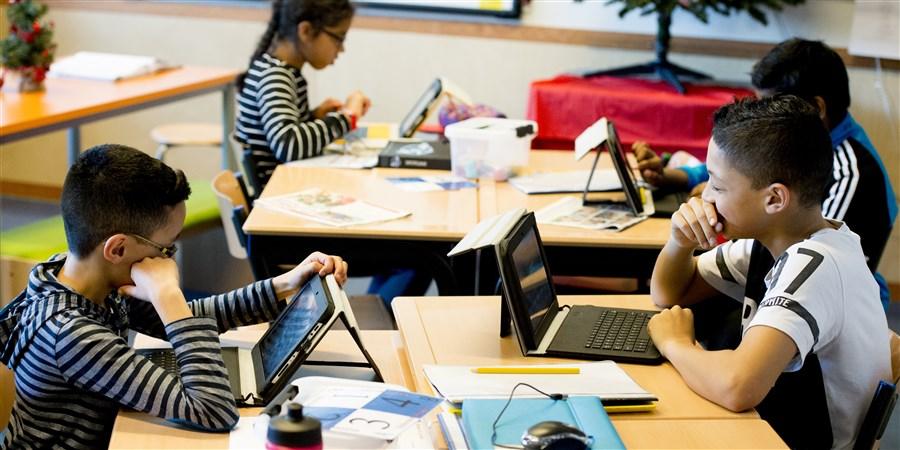 kinderen op basisschool aan het werk met laptop en iPad