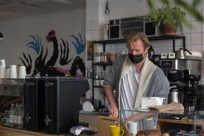 Man maakt espresso in zijn koffiezaak