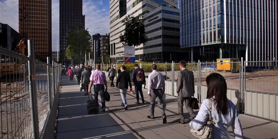 Mensen lopen tussen kantoorgebouwen