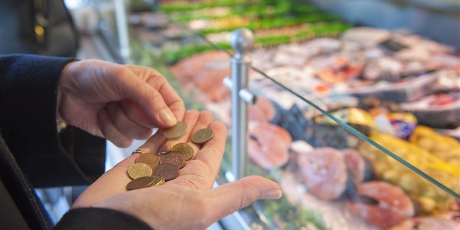 Oudere telt geld bij kassa van slager