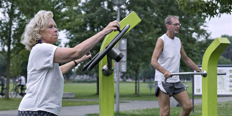 Een vrouw sport in openbare fitness ruimte. Op de achtergrond is haar echtgenoot ook aan het sporten.