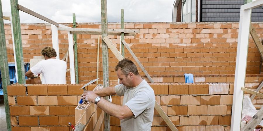 Metselaars in de weer met de aanbouw van een grote vrijstaande woning villa.
