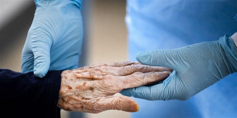 Een fysiotherapeut doet oefeningen met een coronapatient op een speciale cohort-afdeling in een ziekenhuis, waarbij de zorg in handen is van ouderenzorginstellingen.