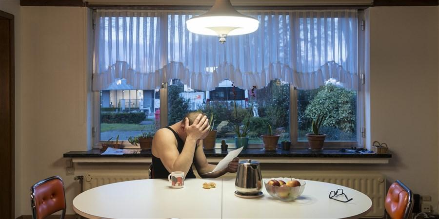 Foto Man leest brief aan eettafel