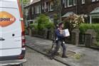 Postbezorger van PostNL levert pakketjes af bij woonhuis