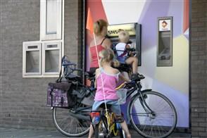 Een vrouw met twee kleine kinderen neemt geld op bij een pinautomaat