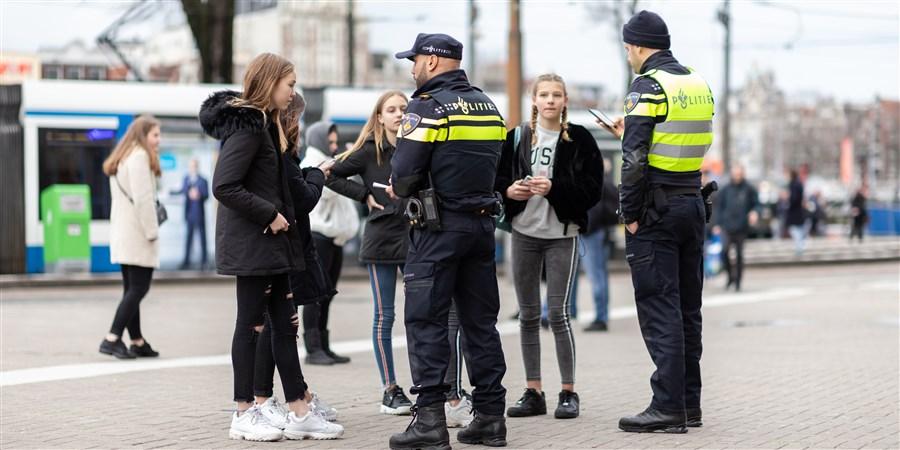 Afbeelding: twee politiemannen die bij groep meisjes staan