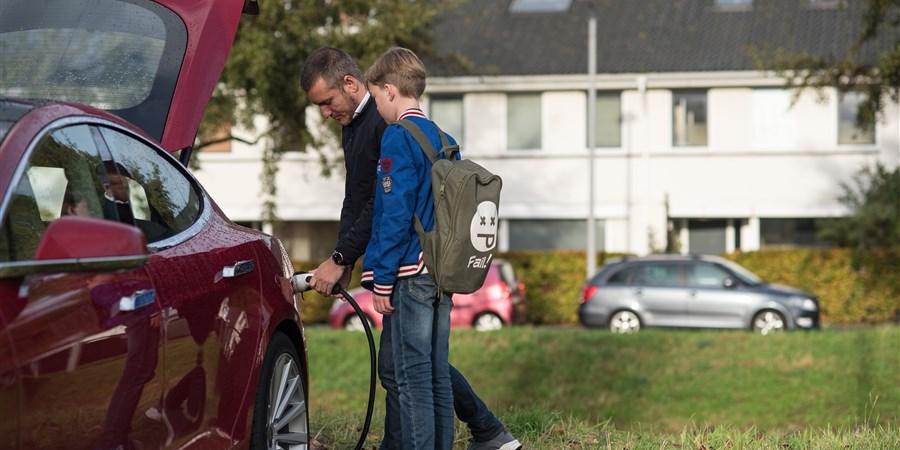 Man haalt, samen met een jongetje, stekker uit een elektrische auto. Zo te zien wordt hij naar school gebracht.