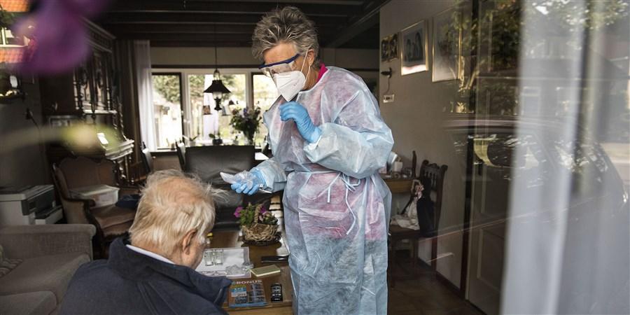 Mevrouw van thuiszorgorganisatie in beschermingskleding. thuiszorg tijdens corona. Een man van 92 wordt thuis verzorgd.