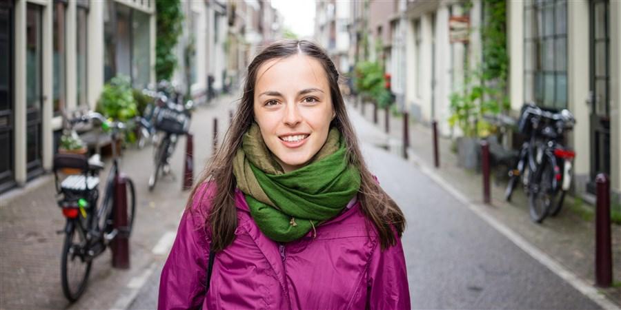Jonge vrouw wandelt door de straten van Amsterdam